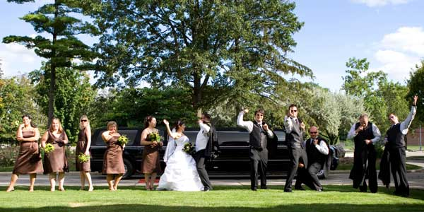 Bride, Groom & Wedding party in front of Stretch SUV Limo