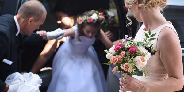 Luxury Chauffeur assisting flowergirl